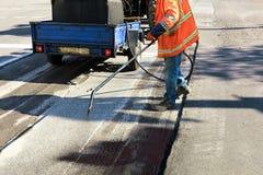 Częściowa naprawa asfaltowa droga Pracownik rozpyla bitum na asfaltowej powierzchni obrazy royalty free