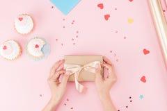 Częściowy odgórny widok ręki zawija prezenta pudełko i wyśmienicie babeczki na menchiach Zdjęcie Royalty Free