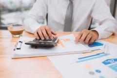 Częściowy widok biznesmen z kalkulatorem pracuje przy miejsce pracy fotografia royalty free