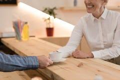 częściowy widok daje filiżance kawy uśmiechnięta kobieta barista Zdjęcia Royalty Free