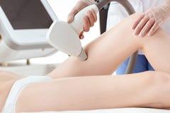 Częściowy widok młodej kobiety usunięcia odbiorcza laserowa włosiana epilacja na udzie Zdjęcia Royalty Free