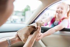 częściowy widok matka w samochodowym daje papierowym pakunku z jedzeniem zdjęcia stock