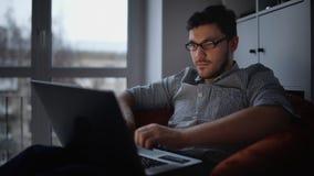 człowiek siedzi młody laptopa zbiory