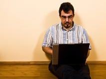 człowiek siedzi na laptopie pracę Obrazy Royalty Free