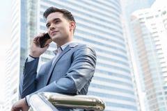 Człowiek z Zachodu Biznesowy mężczyzna opowiada przez mądrze telefonu z drapaczem chmur mnie Fotografia Royalty Free