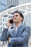 Człowiek z Zachodu Biznesowy mężczyzna opowiada przez mądrze telefonu na społeczeństwie jest Zdjęcia Stock