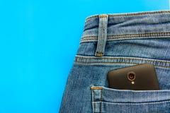 Część telefon komórkowy w niebieskich dżinsach popiera kieszeń zdjęcia stock