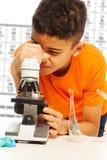 Czarna chłopiec patrzeje w mikroskopie Zdjęcie Royalty Free