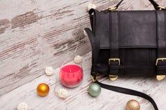 Czarna damy torebka na drewnianym tle, Bożenarodzeniowych ornamentach, girlandzie i świeczce, Zdjęcia Royalty Free