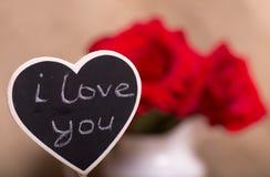 Czarna deska deska z inskrypcją kocham ciebie w postaci serca przeciw czerwonym różom Obrazy Stock