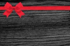 Czarna drewniana tekstura z czerwonym łęku i faborku tłem Zdjęcie Stock