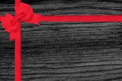 Czarna drewniana tekstura z czerwonym faborku i łęku tłem Fotografia Royalty Free