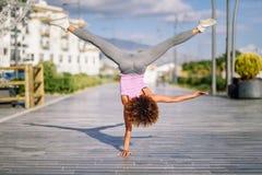 Czarna dysponowana kobieta robi sprawności fizycznych akrobacjom w miastowym tle fotografia royalty free