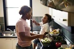Czarna dzieciaka karmienia matka z kulinarnym jedzeniem w kuchni Zdjęcie Stock
