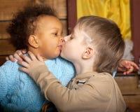 Czarna dziewczyna całuje białej chłopiec Obraz Stock