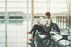 Czarna dziewczyna używa smartphone w poczekalni lotnisko Obrazy Stock
