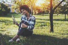 Czarna dziewczyna z cyfrowym pastylki obsiadaniem w parku Fotografia Royalty Free
