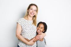 Czarna dziewczyna z jej matką, odosobnioną na szarym tle Obrazy Royalty Free