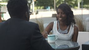 Czarna dziewczyna z trzymać filiżankę kawy, opowiada jej Afro Amerykański kolega, siedzi na zewnątrz kawiarni Fotografia Stock