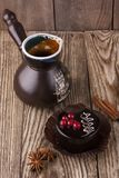 Czarna filiżanka kawy z czekoladowym tortem, cynamonem i anyżem na drewnianym tle, obrazy royalty free