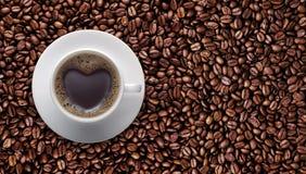 Czarna filiżanka miłość z Kierowym kształtem na kawowej fasoli fotografia stock