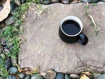 Czarna filiżanka na kamieniu w ogródzie, fotografia royalty free