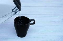 Czarna filiżanka wypełnia z wodą od szklanego teapot na błękitnym drewnianym tle W górę, miejsce dla teksta obraz stock