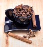 Czarna filiżanka z kawowymi fasolami, anyżem i cynamonem, obraz royalty free