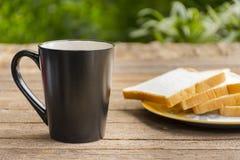 Czarna filiżanka i chlebowy plasterek na drewnianym stole Fotografia Stock