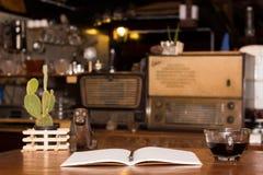Czarna filiżanka i drewniany biurko dzienniczek fotografia royalty free
