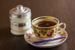Czarna herbaciana filiżanka i cukierniczka na drewnianym stole Zdjęcie Royalty Free