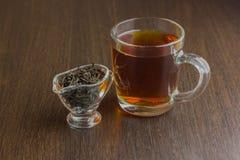 Czarna herbaciana filiżanka i cukierniczka na drewnianym stole Obrazy Stock