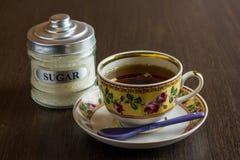 Czarna herbaciana filiżanka i cukierniczka na drewnianym stole Fotografia Stock