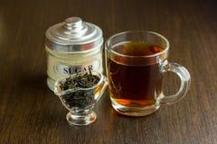 Czarna herbaciana filiżanka i cukierniczka na drewnianym stole Obraz Royalty Free