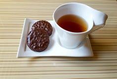 czarna herbata, czekoladowego układu scalonego ciastka, cynamon, cukier, biała filiżanka Zdjęcia Royalty Free