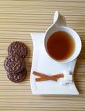 czarna herbata, czekoladowego układu scalonego ciastka, cynamon, cukier, biała filiżanka Zdjęcie Stock
