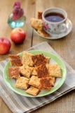 Czarna herbata w filiżance z ciastkami i jabłkami Fotografia Stock