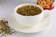 Czarna herbata w szklanej filiżance z mennicą Herbaciani liście w drewnianej łyżce Na białym, odosobnionym tle, obrazy stock