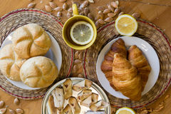 Czarna herbata z cytryną w żółtym kubku z croissants, babeczkami i domowej roboty ciastkami, zdjęcia royalty free