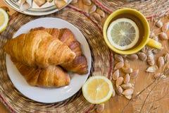 Czarna herbata z cytryną w żółtym kubku z croissants, babeczkami i domowej roboty ciastkami, obrazy stock