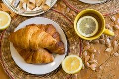Czarna herbata z cytryną w żółtym kubku z croissants, babeczkami i domowej roboty ciastkami, zdjęcie royalty free