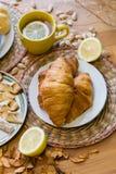 Czarna herbata z cytryną w żółtym kubku z croissants, babeczkami i domowej roboty ciastkami, obraz royalty free