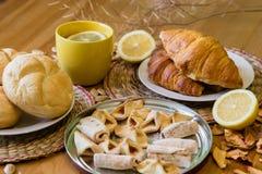 Czarna herbata z cytryną w żółtym kubku z croissants, babeczkami i domowej roboty ciastkami, zdjęcia stock