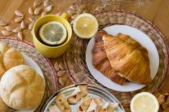 Czarna herbata z cytryną w żółtym kubku z croissants, babeczkami i domowej roboty ciastkami, obrazy royalty free