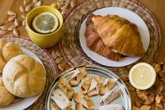 Czarna herbata z cytryną w żółtym kubku z croissants, babeczkami i domowej roboty ciastkami, zdjęcie stock