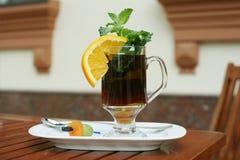 Czarna herbata z pomarańcze, mennicą i wysuszonymi owoc na a, Zdjęcia Stock