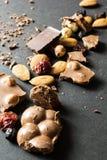 Czarna i dojna czekolada z wysuszonymi owoc na czarnym tle, pionowo obrazy royalty free