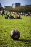 Czarna i pomarańczowa piłka w parku Fotografia Royalty Free