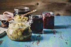 Czarna jagoda, malinka i agrestowy dżem w szkło słojach na błękitnym r, Obraz Stock