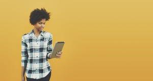 Czarna kędzierzawa dziewczyna z cyfrową pastylką na żółtym tle Obrazy Stock